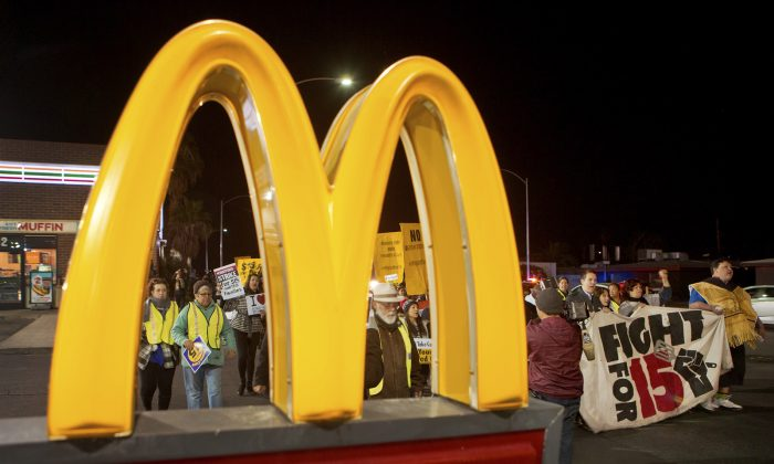 People march during a minimum wage protest, in Las Vegas on Nov. 29, 2016. Fast-food restaurant workers and home and child-care workers participated in protests nationwide for a $15 per hour minimum wage. (L.E. Baskow/Las Vegas Sun via AP)