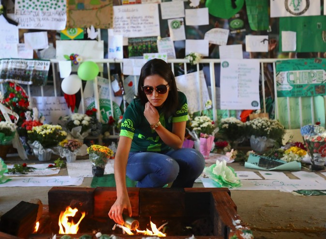 A fan pays tribute to the players of Brazilian team Chapecoense Real at the club's Arena Conda stadium in Chapeco, in the southern Brazilian state of Santa Catarina, on Dec. 1. The players were killed in a plane accident in the Colombian mountains. Players of the Chapecoense team were among the 77 people on board the doomed flight that crashed into mountains in northwestern Colombia. (Buda Mendes/Getty Images)