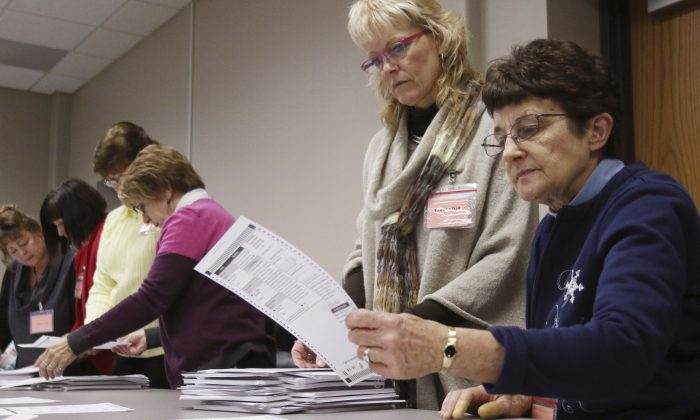 Tabulator Claudette Moll (R) from Farmington, looks over a ballot during a statewide presidential election recount West Bend, Wis., on Dec. 1, 2016. (John Ehlke/West Bend Daily News via AP)