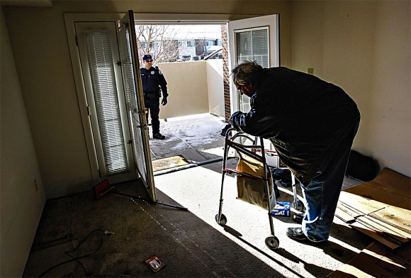 An officer waits to escort Harvey Lesser, an unemployed software developer, from his apartment after serving him with a court order for eviction in Boulder, Colo., on Dec. 11, 2009.
