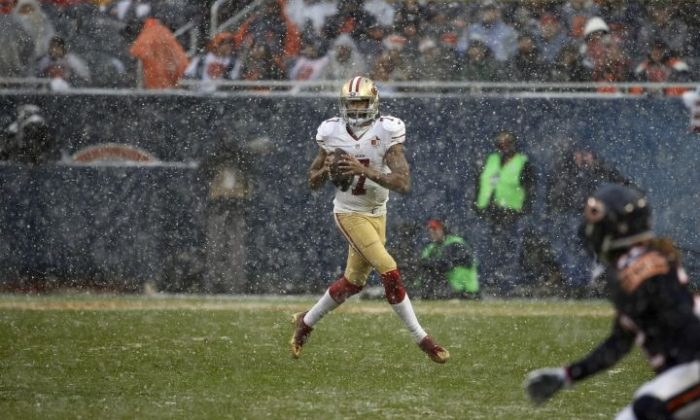 San Francisco 49ers quarterback Colin Kaepernick (7) rolls out as he looks for a receiver during the second half of an NFL football game against the Chicago Bears, Sunday, Dec. 4, 2016, in Chicago. (AP Photo/Charles Rex Arbogast)
