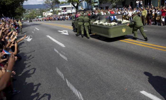 Soldiers push the jeep and trailer carrying the ashes of the late Fidel Castro after the jeep briefly stopped working during Castro's funeral procession near Moncada Fort in Santiago, Cuba, Saturday, Dec. 3, 2016. Castro's ashes will be interred Sunday in Santiago, ending a nine-day period of mourning that saw Cuba fall silent as thousands paid tribute to photographs of Castro and sign oaths of loyalty to his socialist, single-party system. (AP Photo/Rodrigo Abd)