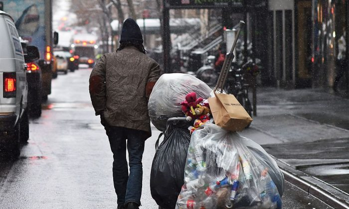 A man walks with a cart of recyclable bottles and cans along a street during a wet snowfall in New York on March 4, 2016 (JEWEL SAMAD/AFP/Getty Images)