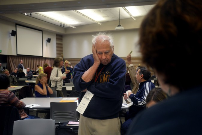 Burke Cueny, of Rochester, watches as volunteers and city officials participate in a recount after a federal judge ordered the statewide recount at the Oakland Schools Conference Center in Waterford Township, Michigan on Dec. 5, 2016. Three people have now filed a lawsuit to get a hand recount in Florida. (Rachel Woolf/Getty Images)