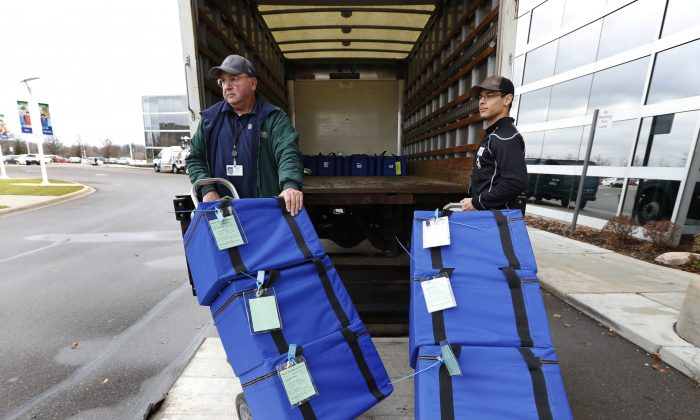 Ballots are unloaded during a statewide presidential election recount in Waterford Township, Mich.  on Dec. 5, 2016. A judge ordered a hand recount of Michigan's presidential results. (AP Photo/Paul Sancya)