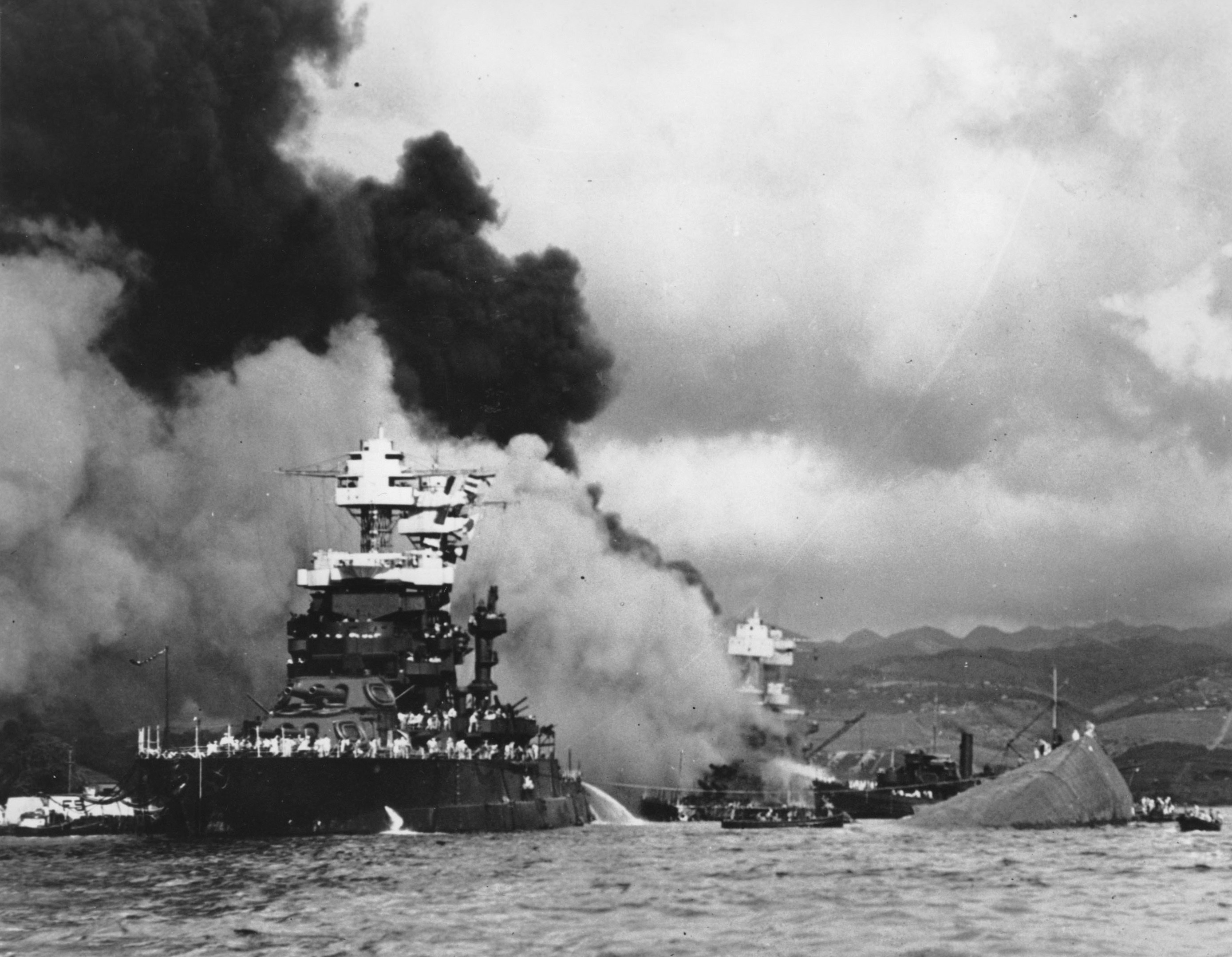 Part of the hull of the capsized USS Oklahoma is seen at right as the battleship USS West Virginia (C) begins to sink after suffering heavy damage, while the USS Maryland (L) is still afloat in Pearl Harbor, Oahu, Hawaii, in this file photo. (AP Photo/U.S. Navy)