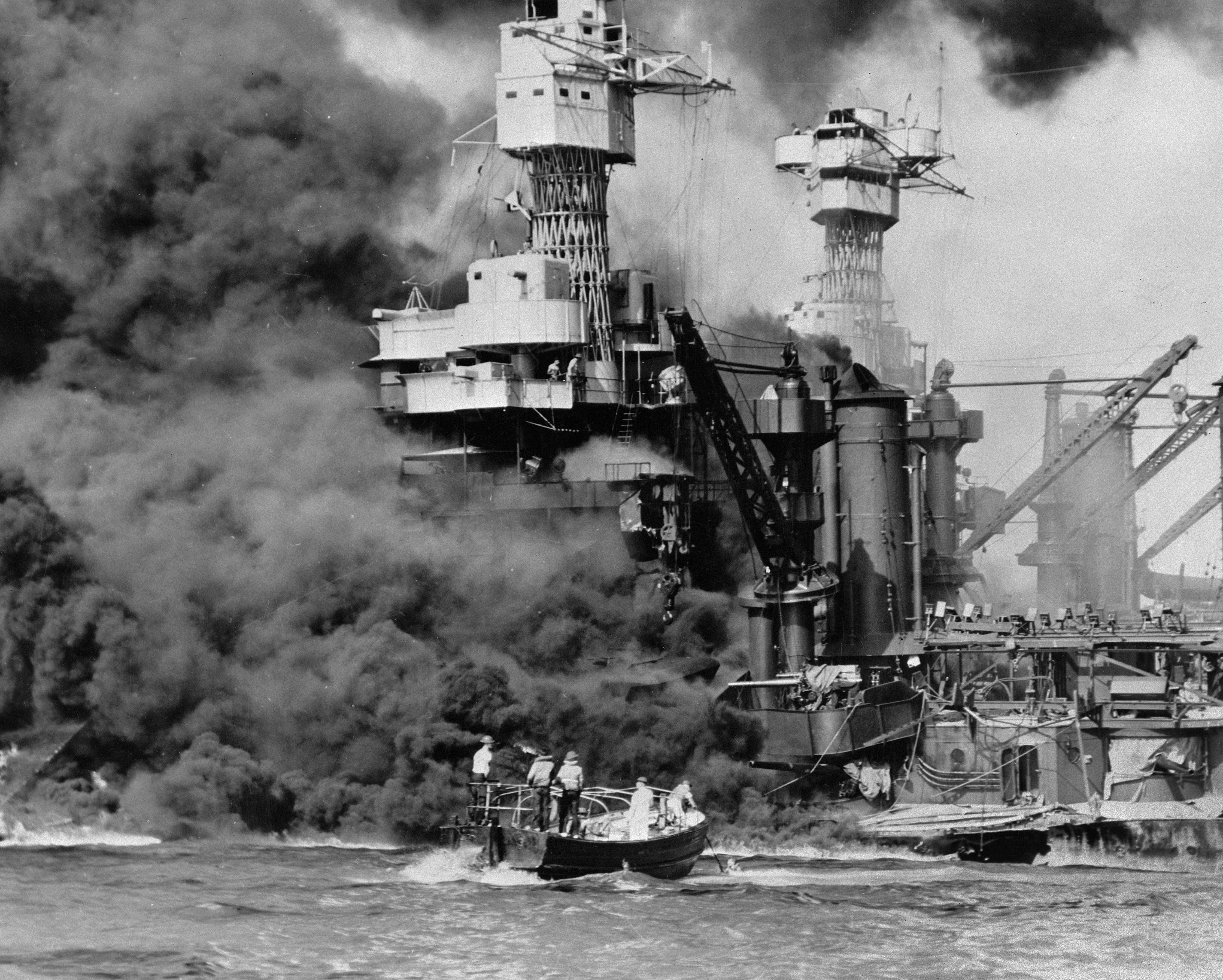 A small boat rescues a seaman from the USS West Virginia burning in the foreground in Pearl Harbor, Hawaii on Dec. 7. (U.S. Navy via AP)
