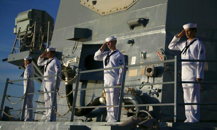 A Navy sailors aboard the USS Halsey salute the USS Utah Memorial, in Honolulu on Dec. 7, 2016. (AP Photo/Marco Garcia)