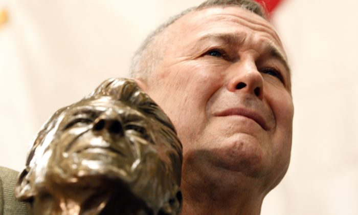 Rep. Dana Rohrabacher, R- Calif., holds a bust of Ronald Reagan as he listens to Republican presidential hopeful former Massachusetts Gov. Mitt Romney campaign at Bassett Furniture in Fountain Valley, Calif., Thursday, Jan. 31, 2008. (AP Photo/LM Otero )