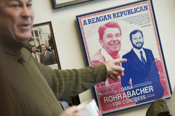 Rep. Dana Rohrabacher, R-Calif., talks about a campaign poster with his image alongside Ronald Reagan's while giving a tour of his Rayburn Building office to Roll Call.  (Tom Williams/Roll Call) (CQ Roll Call via AP Images)