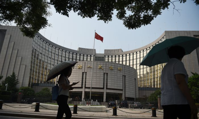 Pedestrians walk past the People's Bank of China, the central bank of China, in Beijing July 8, 2015. (Greg Baker/AFP/Getty Images)