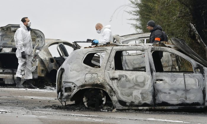 French police officers investigate on the highway where thieves robbed an armored truck loaded with gold in Dardilly, near Lyon, central France on Dec. 12, 2016. French police say a manhunt is underway for four thieves who have stolen dozens of kilograms of gold from an armored truck before setting it ablaze on a major highway. (AP Photo/Laurent Cipriani)