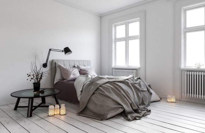 Large windows and minimal furniture is a simple, classic style. The messy bed is also a characteristic of Scandinavian design.  (PlusONE/Shutterstock)