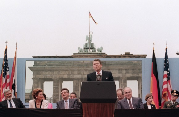 """US President Ronald Reagan, commemorating the 750th anniversary of Berlin, addresses the people of West Berlin at the base of the Brandenburg Gate, near the Berlin wall on Jun. 12, 1987. Due to the amplification system being used, the President's words could also be heard on the Eastern (Communist-controlled) side of the wall. """"Tear down this wall!"""" was the famous command from United States President Ronald Reagan to Soviet leader Mikhail Gorbachev to destroy the Berlin Wall. The address Reagan delivered that day is considered by many to have affirmed the beginning of the end of the Cold War and the fall of communism. On Nov. 9-11, 1989, the people of a free Berlin tore down that wall. (MIKE SARGENT/AFP/Getty Images)"""