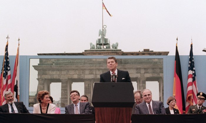 """U.S. President Ronald Reagan, commemorating the 750th anniversary of Berlin, addresses the people of West Berlin at the base of the Brandenburg Gate, near the Berlin wall on Jun. 12, 1987. Due to the amplification system being used, the President's words could also be heard on the Eastern (Communist-controlled) side of the wall. """"Tear down this wall!"""" was the famous command from United States President Ronald Reagan to Soviet leader Mikhail Gorbachev to destroy the Berlin Wall. On Nov. 9-11, 1989, the people of a free Berlin tore down that wall. (MIKE SARGENT/AFP/Getty Images)"""