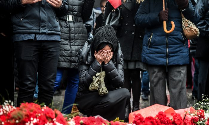 A woman reacts at the site of an explosion where flowers have been placed for the victims of the Dec. 10 blasts, outside Besiktas' Vodafone Arena football stadium on Dec. 13, 2016 in Istanbul.  Twin blasts hit Istanbul on December 10, 2016 killing 37 police officers and seven civilians. (OZAN KOSE/AFP/Getty Images)