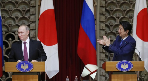 Japanese Prime Minister Shinzo Abe, right, applauds as Russian President Vladimir Putin reacts during their joint press conference in Tokyo, Japan, on Dec. 16, 2016. (AP Photo/Alexander Zemlianichenko, Pool)