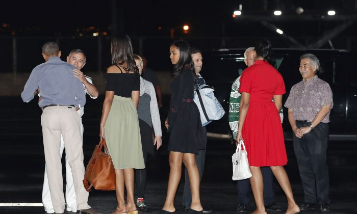 U.S. President Barack Obama, left, and first lady Michelle Obama, second from right, with their daughters Malia, third from left, and Sasha, fifth from left, are greeted as they arrive on Air Force One, Friday, Dec. 16, 2016, at Joint Base Pearl Harbor-Hickam, adjacent to Honolulu, Hawaii, for their annual family vacation on the island of Oahu. Greeting the first family from left are Adm. Harry Harris, commander of the U.S. Pacific Command, and his wife Bruni Bradley, Sen. Brian Schatz, D-Hawaii, Mayor of Honolulu Kirk Caldwell, and Hawaii Gov. David Ige. (AP Photo/Carolyn Kaster)