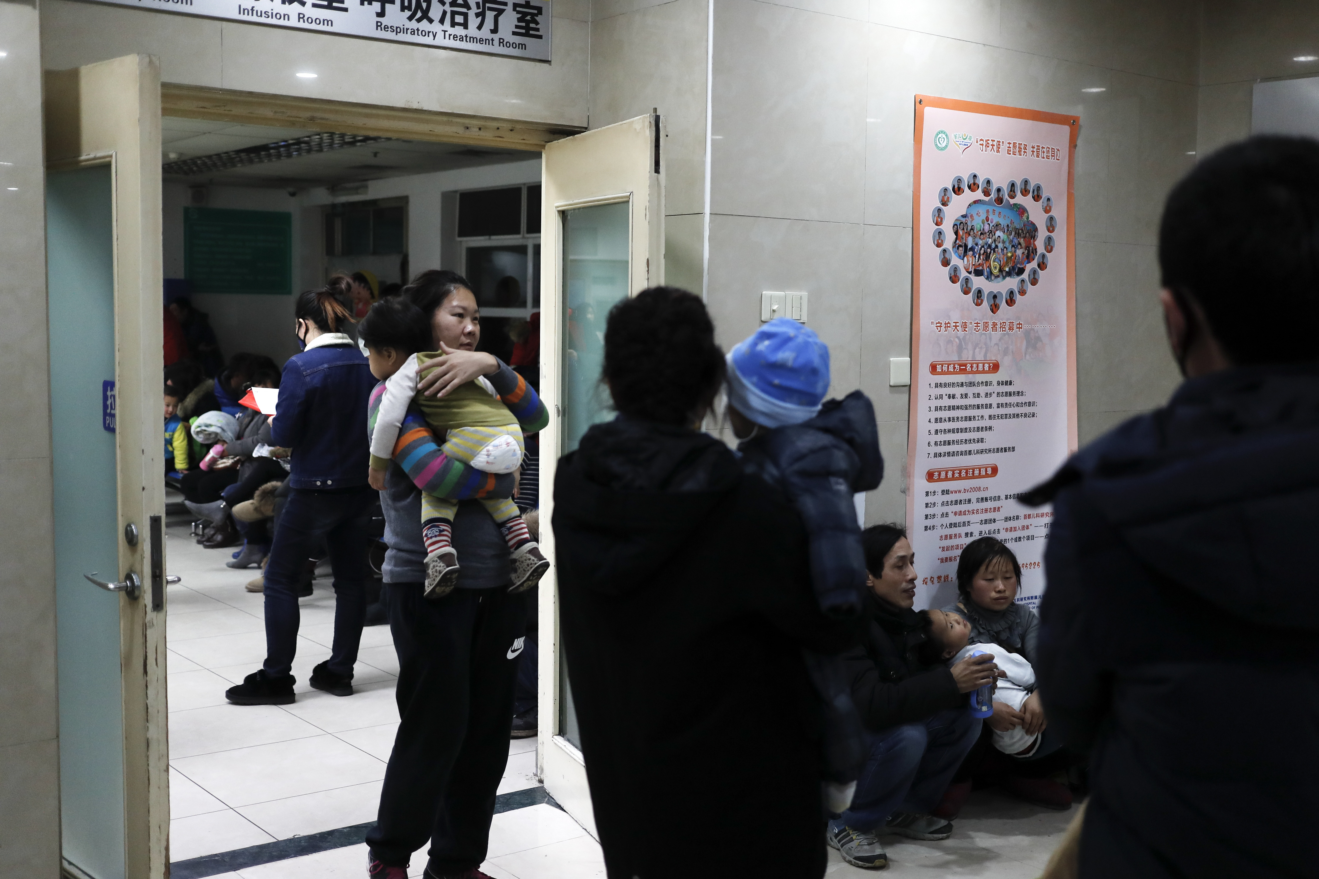 Parents carrying their children wait to see doctors at a children's hospital in Beijing on Dec. 18, 2016. (AP Photo/Andy Wong)