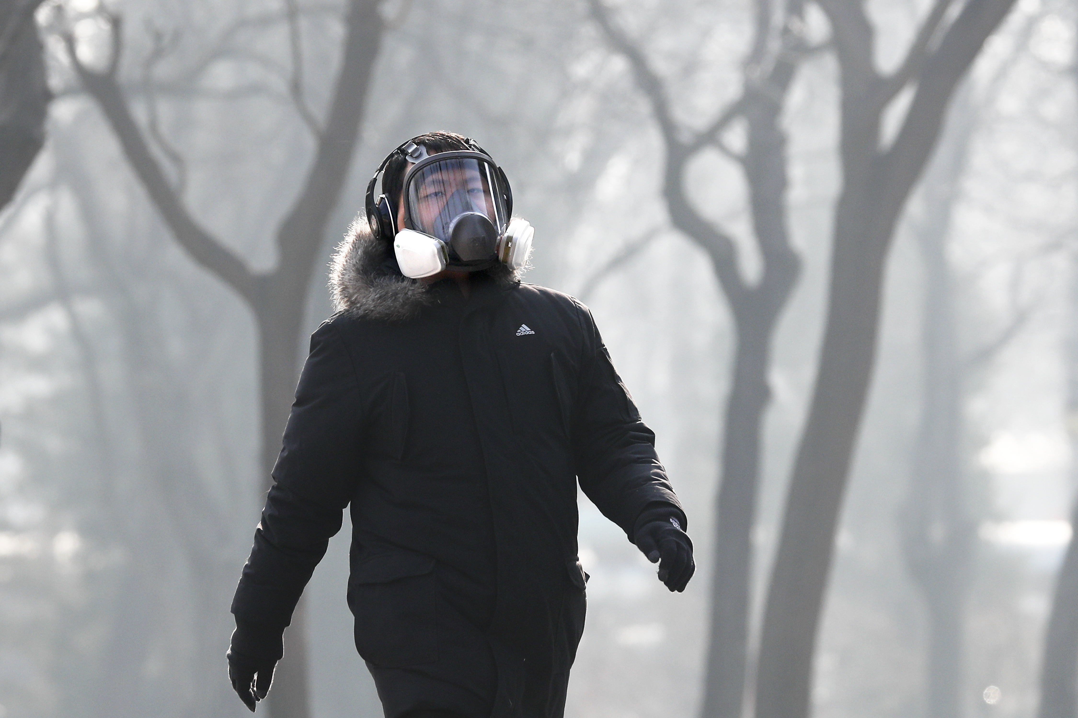 A man wearing a mask for protection against pollution exercise at Ritan Park during a heavily polluted day in Beijing, on Dec. 19, 2016. (AP Photo/Andy Wong)