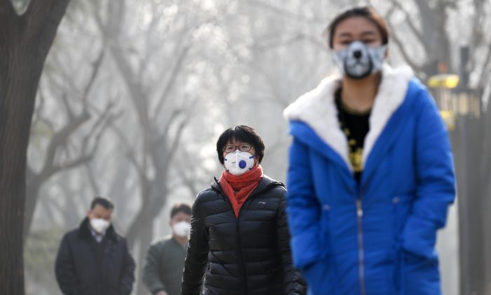 Chinese people wearing masks for protection against pollution walk at Ritan Park shrouded by heavy smog in Beijing, on Dec. 19, 2016. (AP Photo/Andy Wong)