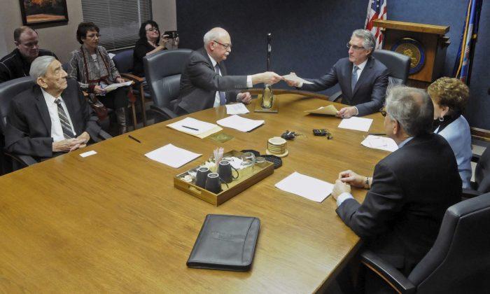 North Dakota's Secretary of State Al Jaeger (L) hands Gov. Doug Burgum voting results of the North Dakota Electoral College in Bismarck, N.D.  on Dec. 19, 2016. (Tom Stromme/The Bismarck Tribune via AP)