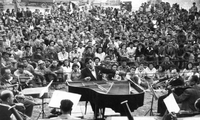 Leonard Bernstein of New York conduct the Israel Philharmonic Orchestra for a military audience at Beersheba, Israel, the ?desert capital of the Negev,? Nov. 1948. (AP Photo)