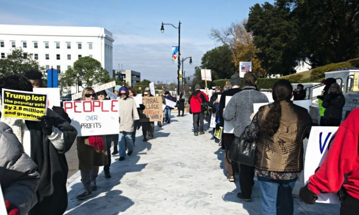 Protesters march outside the Alabama Capitol building requesting that electoral college delegates abstain from voting for President-elect Donald Trump on Monday, Dec. 19, 2016, in Montgomery, Ala. Alabama's nine presidential electors have all cast their ballots for Republican president-elect Donald Trump. (Albert Cesare/The Montgomery Advertiser via AP)