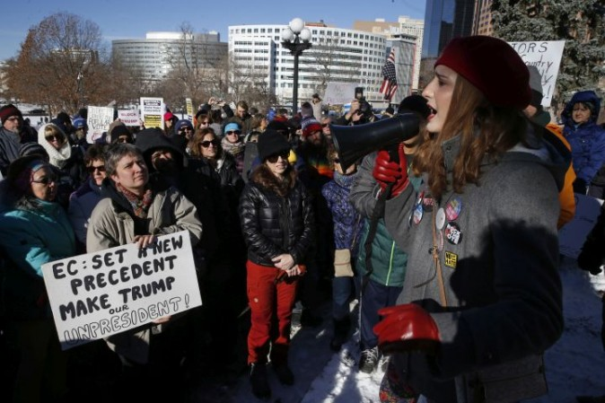 Protestors rally outside the Capitol in Denver, Monday, Dec. 19, 2016, in hopes of persuading the Colorado Electoral College members to join a long-shot national effort to block President-elect Donald Trump. (AP Photo/Brennan Linsley)