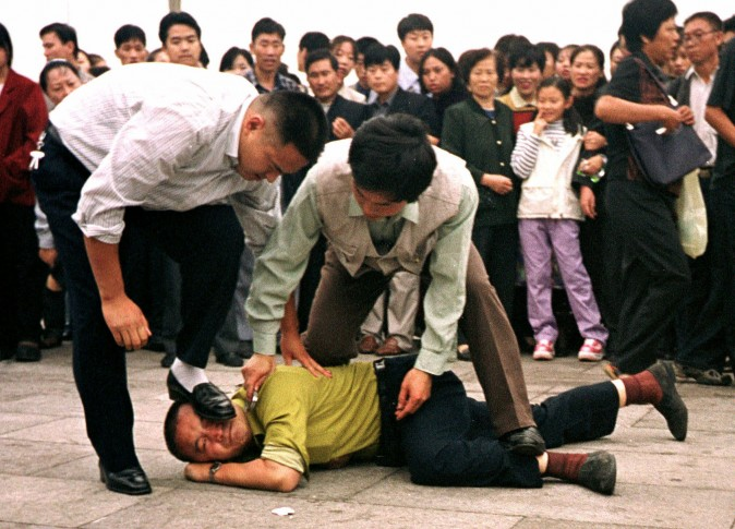 Police detain a Falun Gong protester in Tiananmen Square on Oct. 1, 2000. In January 2017, the Chinese regime appeared to publicly indicate that the persecution campaign remains an official policy. (AP Photo/Chien-min Chung)