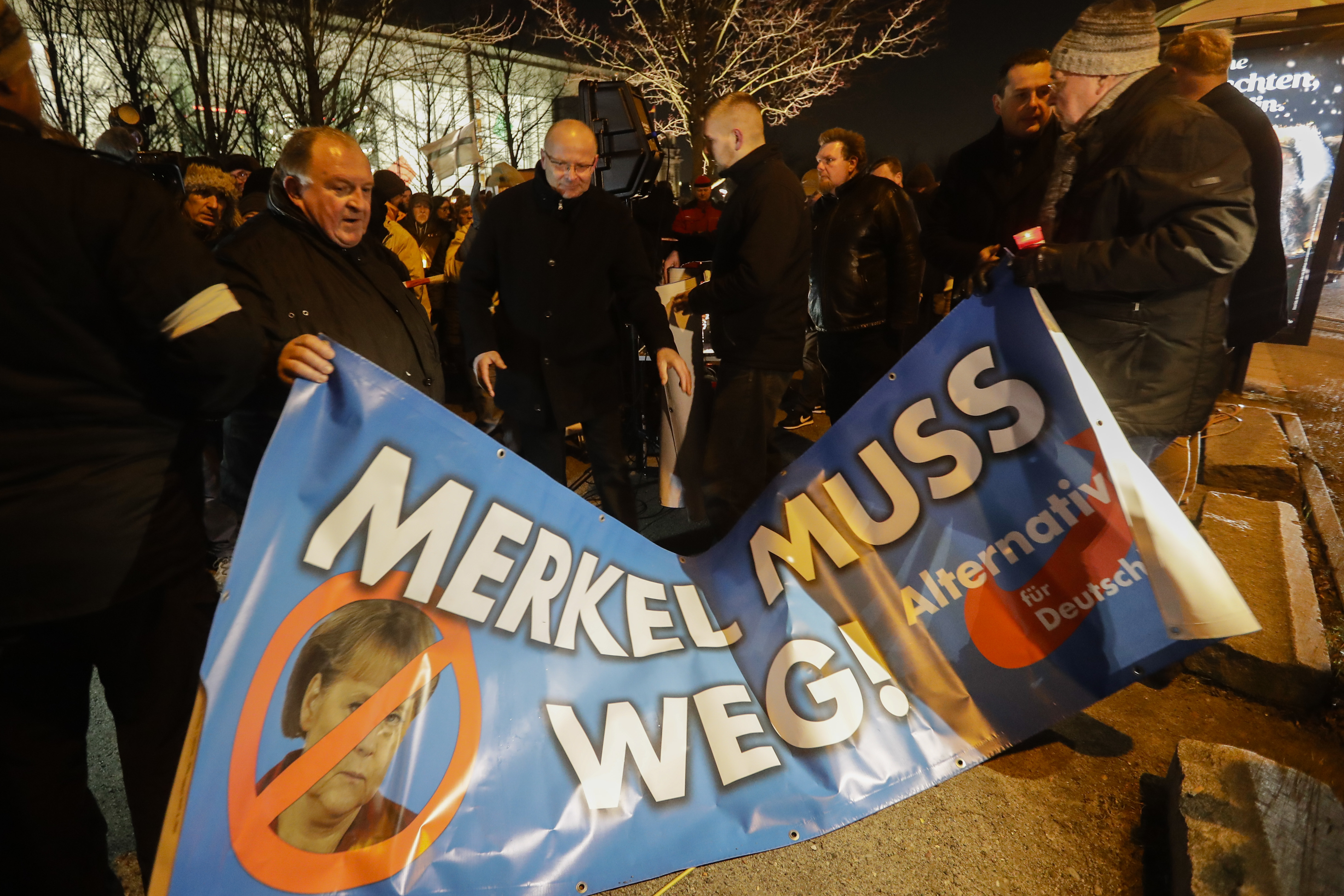 People hold a poster reading: 'Merkel must go' as they attend a demonstration of the Alternative for Germany, AfD, in front of the Chancellery in Berlin on Dec. 21, 2016. (AP Photo/Markus Schreiber)
