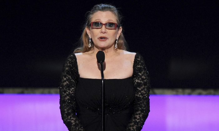 In this Sunday, Jan. 25, 2015 file photo, Carrie Fisher presents the life achievement award on stage at the 21st annual Screen Actors Guild Awards at the Shrine Auditorium in Los Angeles. Fisher has reportedly been transported to a hospital after suffering a severe medical emergency on a flight Friday, Dec. 23, 2016. (Photo by Vince Bucci/Invision/AP, File)