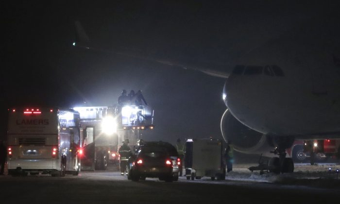 Players, coaches and staff from the Minnesota Vikings are taken off a plane in small groups at Appleton International Airport on Friday, Dec. 23, 2016, in Appleton, Wis. The NFL football team' plane slid off a runway and became stuck in the grass, leaving players waiting for hours to get off the aircraft. A team spokesman says there were no injuries after the landing shortly after 5 p.m. The Vikings will play the Green Bay Packers on Saturday. (Danny Damiani/The Post-Crescent via AP)