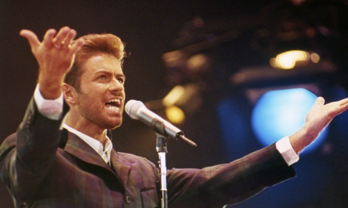 """In this Dec. 2, 1993 file photo, George Michael performs at """"Concert of Hope"""" to mark World AIDS Day at London's Wembley Arena. According to a publicist on Dec. 25, 2016, the singer has died at the age of 53. (AP Photo/Gill Allen)"""
