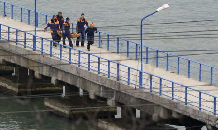 Russian rescue workers carry a body from the wreckage of the crashed plane, at a pier just outside Sochi, Russia, Sunday, Dec. 25, 2016. Russian ships, helicopters and drones are searching for bodies after a plane carrying 93 people crashed into the Black Sea. The plane was taking the Alexandrov Ensemble, a military choir, to perform at Russia's air base in Syria when it went down shortly after takeoff. (AP Photo/Viktor Klyushin)