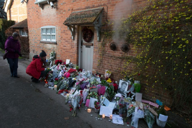 People look at the tributes outside the home of British singer George Michael in the village of Goring, England, on Dec. 27, 2016, where the singer died of apparent heart failure on Christmas Day. (Daniel Leal-Olivas/AFP/Getty Images)