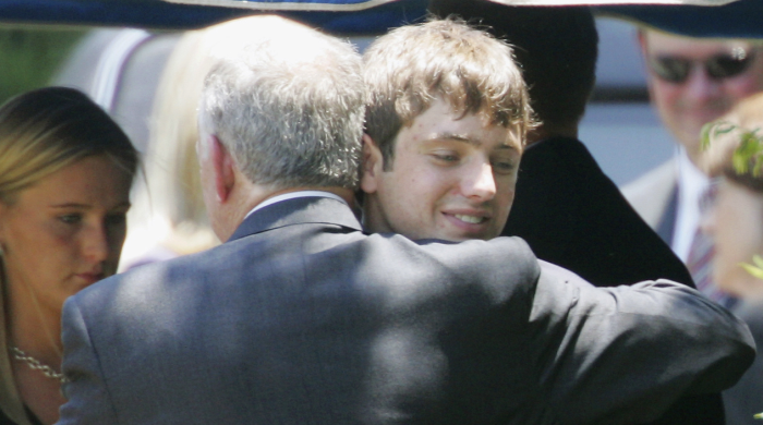 In this June 29, 2006, file photo, John Ramsey hugs his son, Burke (facing camera) at the graves of his wife, Patsy, and daughter, JonBenet, during services for his wife at the St. James Episcopal Cemetery in Marietta, Georgia. Burke Ramsey sued CBS and others for $750 million over a series that aired in September 2016 that Ramsey alleges concluded he killed his sister. (AP Photo/Ric Feld, File)