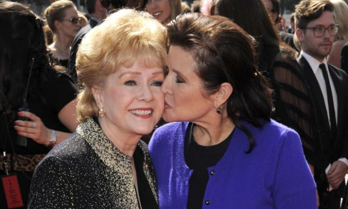 """FILE- In this Sept. 10, 2011, file photo, Debbie Reynolds, left, and Carrie Fisher arrive at the Primetime Creative Arts Emmy Awards in Los Angeles. Reynolds, star of the 1952 classic """"Singin' in the Rain"""" died Wednesday, Dec. 28, 2016, according to her son Todd Fisher. She was 84. (AP Photo/Chris Pizzello, File)"""