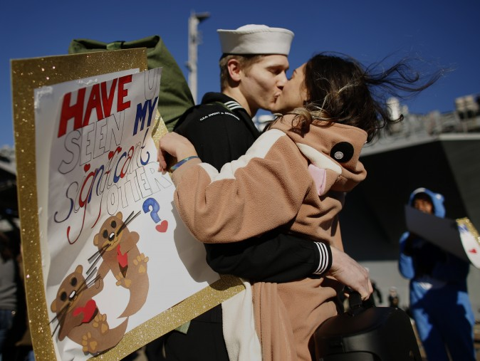 "Melanie Till, in costume and carrying a sign reading ""Have u seen my significant otter?"", welcomes home her husband P.O. 3rd Class David Till at Naval Station Norfolk, in Norfolk, Va., on Dec, 30, 2016, from a seven-month deployment to the Middle East and the Mediterranean Sea. (Stephen M. Katz/The Virginian-Pilot via AP)"