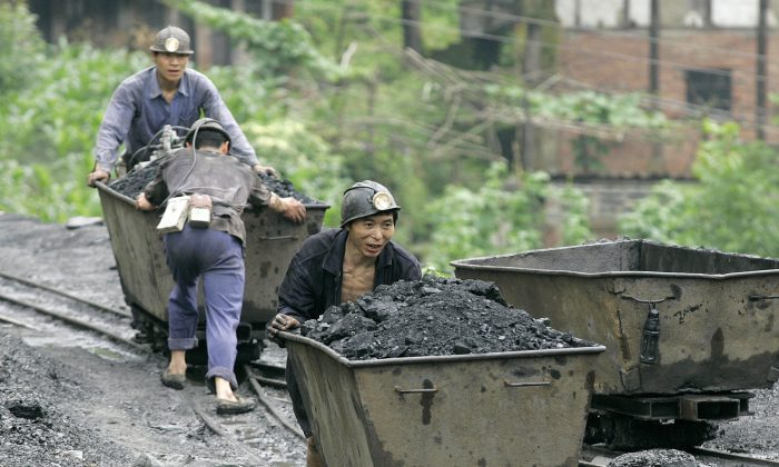In a file photo, miners push carts containing coal at a mine in Qianwei county, Sichuan. (Liu Jin/AFP/Getty Images)
