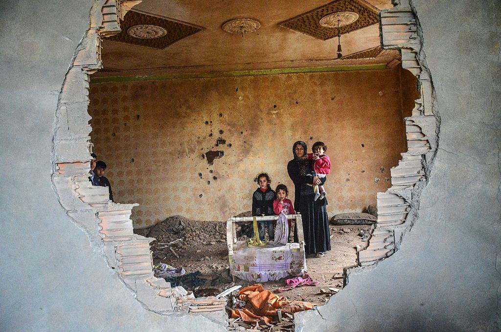 A woman and her children in the ruins of their battle-damaged house in the Kurdish town of Silopi, Turkey, on Jan. 19. (ILYAS AKENGIN/AFP/Getty Images)