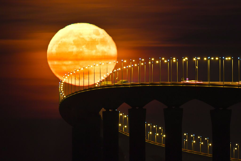 A full moon rising over the Re Island Bridge in Rivedoux is pictured on December 14, 2016. (XAVIER LEOTY/AFP/Getty Images)