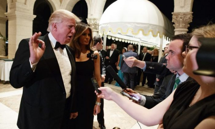 Melania Trump, right, looks on as her husband President-elect Donald Trump talks to reporters during a New Years Eve party at Mar-a-Lago, Saturday, Dec. 31, 2016, in Palm Beach, Fla. (AP Photo/Evan Vucci)