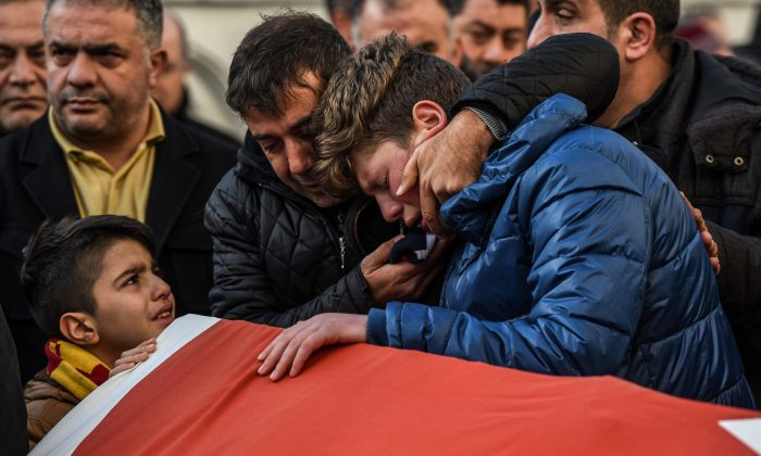 Relatives and friends mourn at a coffin in Istanbul on Jan. 1, during the funeral of Ayhan Arik, one of the 39 victims of the gun attack on the Reina nightclub. (OZAN KOSE/AFP/Getty Images)