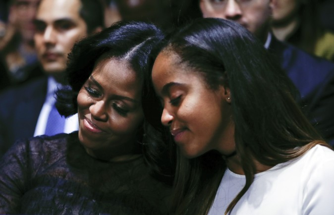 First lady Michelle Obama and daughter Malia lean into one another as they listen to President Barack Obama speak during his farewell address at McCormick Place in Chicago, Tuesday, Jan. 10, 2017. (AP Photo/Pablo Martinez Monsivais)