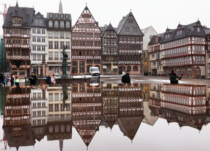 The timber-frame houses at the Roemerberg square are reflected in water in Frankfurt, Germany, on Jan. 11, 2017. (AP Photo/Michael Probst)