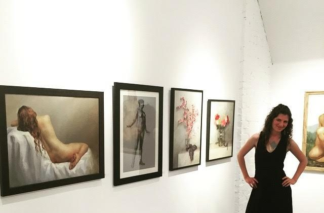 Mandy Hallenius in front of her paintings at an exhibit. (Courtesy of Mandy Hallenius)