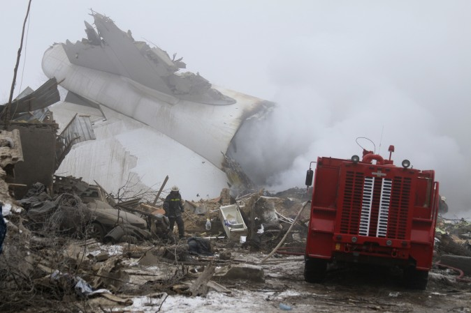 A Kyrgyz firefighter inspects a plane crash site outside Bishkek, Kyrgyzstan, on Jan. 16. A Turkish Boeing 747 cargo plane crashed just outside the Manas airport Monday morning killing people in the residential area adjacent to the Manas airport as well as those on the plane. (AP Photo/Azamat Imanaliev)