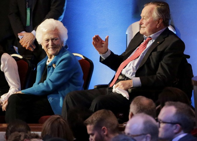 Former President George H. W. Bush (R) and his wife, Barbara, are greeted before a Republican presidential primary debate at The University of Houston in Houston, in this file photo. (AP Photo/David J. Phillip)