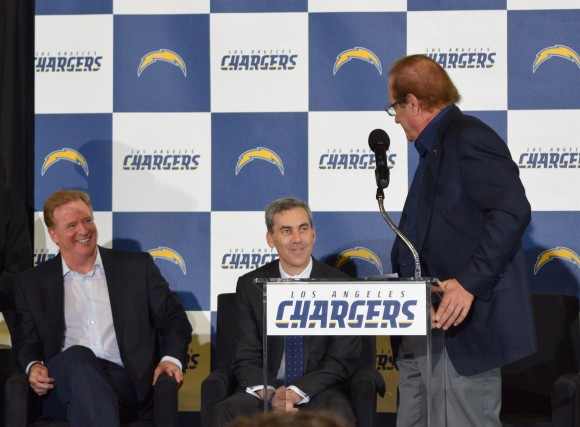 Chargers owner Dean Spanos (R) tells Rams COO Kevin Demoff that he hopes the teams face off at the Superbowl, while NFL Commissioner Roger Goodell (L) laughs, in Inglewood, Calif. on Jan. 18. (Sarah Le/Epoch Times)